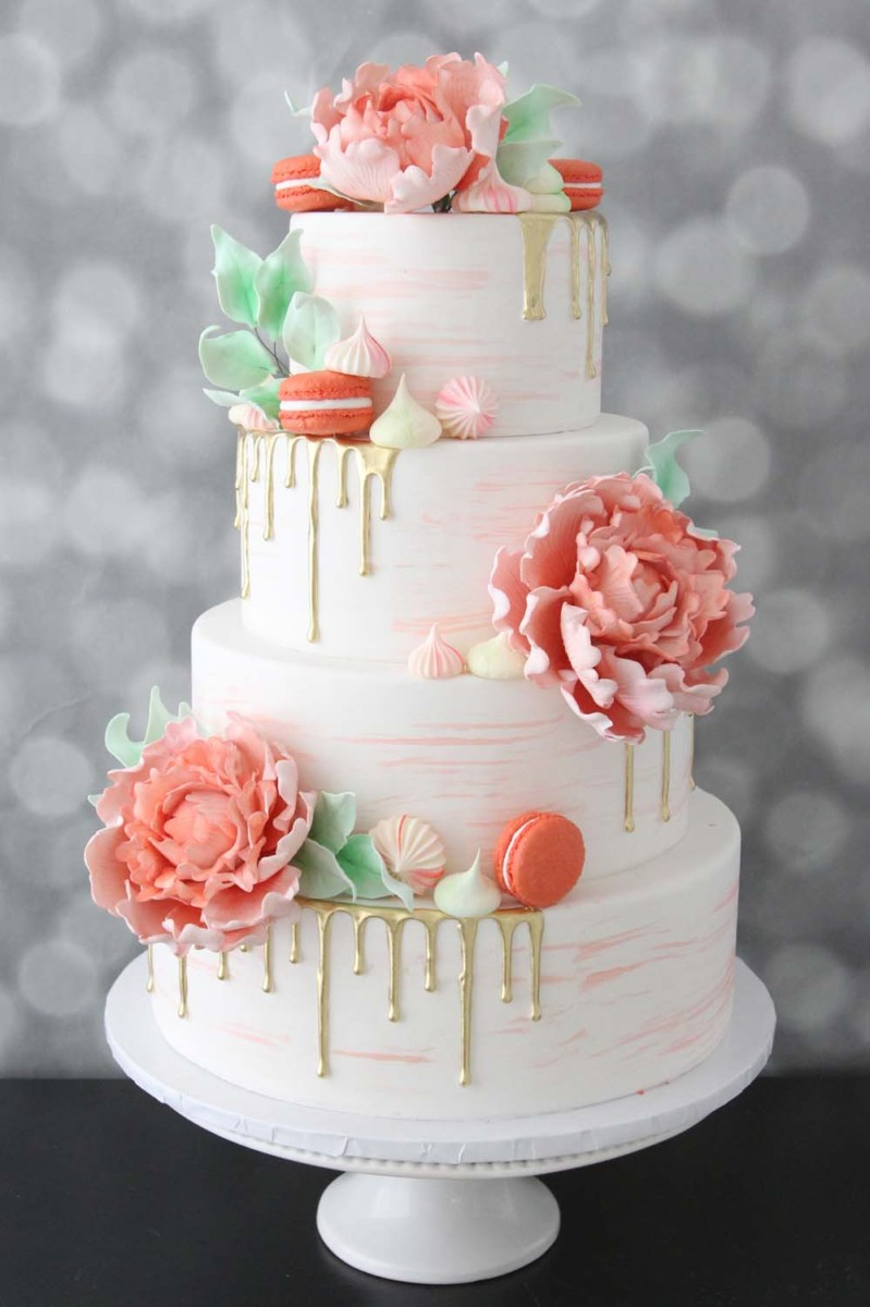 pantone color of the year living coral wedding cake trend with gold drip, macarons, and meringue details