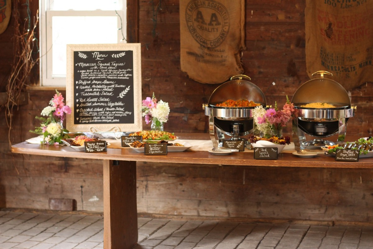 raritan inn wedding buffet table inside barn with chalkboard menu and chafers